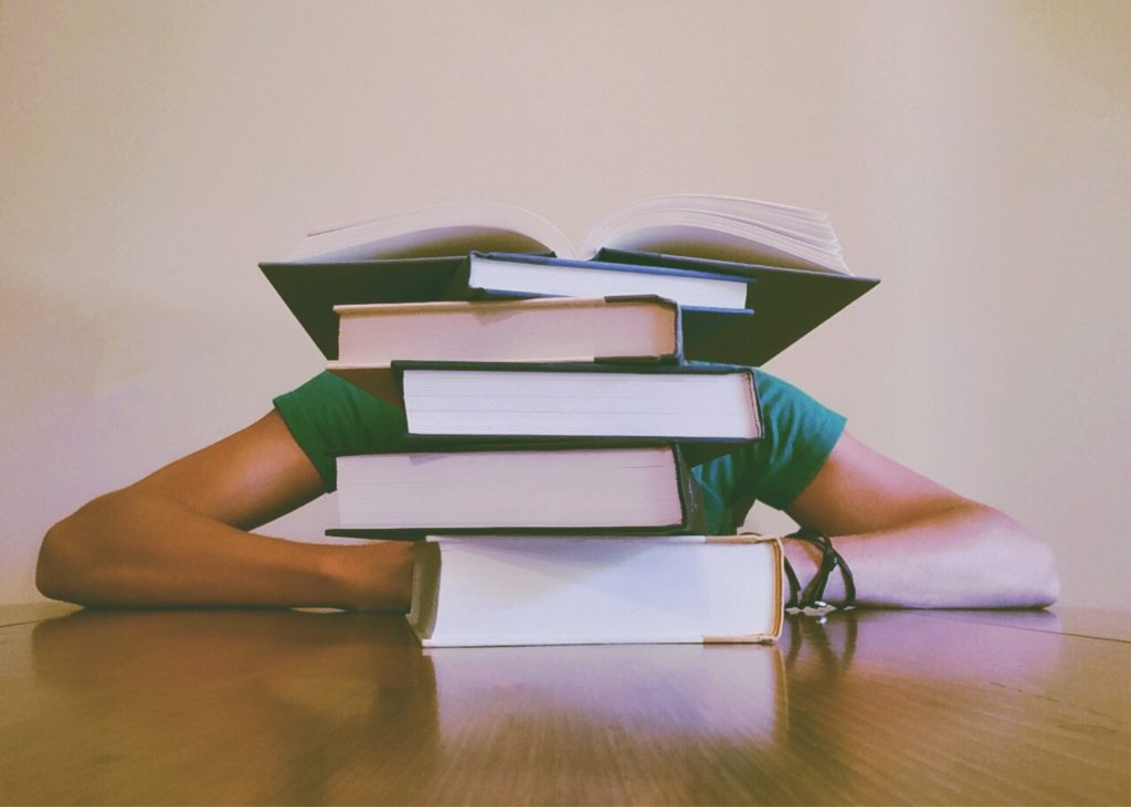 A person is hidden behind a pile of books on a table. Let me teach you about naturopathic medicine instead.